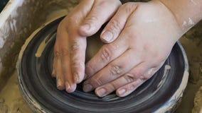 Las manos de la afición de la artesanía de la cerámica amasan la rueda puesta arcilla almacen de metraje de vídeo