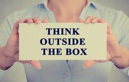 Las manos de la empresaria que llevan a cabo la muestra blanca con el mensaje piensan fuera de la caja fotografía de archivo libre de regalías