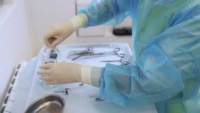 Las manos de la enfermera del primer en guantes estéril preparan los instrumentos médicos para la cirugía sclerotherapy almacen de metraje de vídeo