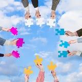 Las manos de la gente con rompecabezas juntan las piezas con las nubes blancas Foto de archivo libre de regalías