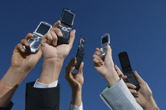 Las manos de la gente de negocio que sostienen los teléfonos móviles Imagenes de archivo
