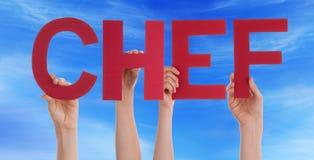 Las manos de la gente detienen al cocinero recto rojo Blue Sky de la palabra Foto de archivo libre de regalías