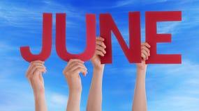 Las manos de la gente sostienen el cielo azul de junio de la palabra recta roja Imagen de archivo