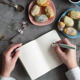 Las manos de la hembra dos llevan a cabo una nota vacía El diseñador dibuja bosquejos en el descanso para tomar café de la tabla  foto de archivo libre de regalías