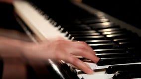 Las manos de la hembra que juegan el piano de cola, primer metrajes