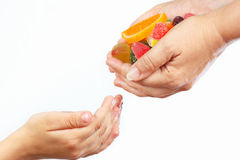 Las manos de la madre dan los caramelos y los dulces coloridos en cierre del niño de las manos para arriba Fotografía de archivo libre de regalías
