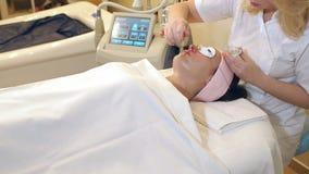 Las manos de la mancha del cosmetologist con una crema del cepillo en la cara de una muchacha metrajes