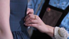 Las manos de la modista que modifican el vestido para requisitos particulares en cliente almacen de video