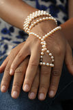 Las manos de la muchacha africana con las perlas Foto de archivo libre de regalías