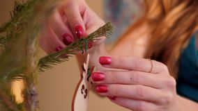Las manos de la muchacha cercana de la cámara lenta cuelgan el conejo en el árbol de navidad metrajes