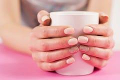 Las manos de la muchacha con abarrotan de los clavos de la manicura que sostienen la taza de café en el escritorio rosado Fotos de archivo libres de regalías