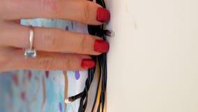 Las manos de la muchacha del primer fijan la guirnalda del árbol de navidad alrededor de imagen almacen de metraje de vídeo