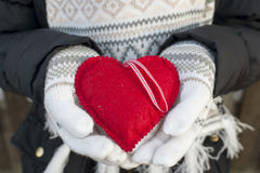 Las manos de la muchacha en blanco hicieron punto las manoplas con el corazón rojo romántico imagen de archivo libre de regalías