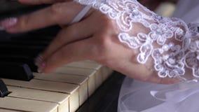 Las manos de la muchacha en los guantes blancos con una manicura hermosa jugar el piano Juegue la melodía en las notas M?sica almacen de metraje de vídeo