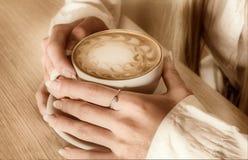 Las manos de la muchacha guardan el café de la taza Fotos de archivo