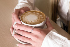 Las manos de la muchacha guardan el café de la taza Foto de archivo libre de regalías