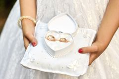 Las manos de la muchacha llevan a cabo los anillos de bodas en una caja en forma de coraz?n fotografía de archivo