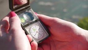 Las manos de la muchacha que abren el dispositivo multifuncional del compás Primer extremo con la corriente del río en el fondo almacen de video