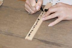 Las manos de la muchacha que escriben deseos personales en japonés en una boa del rezo Fotografía de archivo