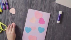 Las manos de la muchacha que pegan una tarjeta Día del `s de la tarjeta del día de San Valentín almacen de video