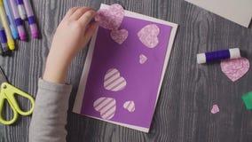 Las manos de la muchacha que pegan una tarjeta Día del `s de la tarjeta del día de San Valentín almacen de metraje de vídeo