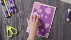Las manos de la muchacha que pegan una tarjeta Día del `s de la tarjeta del día de San Valentín metrajes