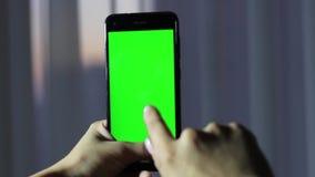 Las manos de la muchacha que sostienen un teléfono móvil con una pantalla verde llave del hroma metrajes