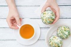 Las manos de la muchacha que sostienen una taza de té y de torta imagen de archivo
