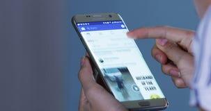 Las manos de la mujer abren Facebook app en smartphone almacen de video