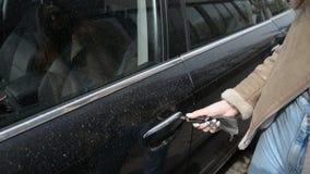 Las manos de la mujer abren la puerta del coche en el primer, sistemas en el coche y cierran la puerta almacen de metraje de vídeo