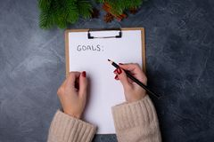 Las manos de la mujer alistan para escribir metas en lista en blanco en fondo oscuro Endecha plana Visión superior Concepto del A imagenes de archivo