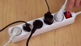 Las manos de la mujer apagan el interruptor de la extensión de la electricidad y desenchufan los alambres almacen de video