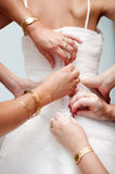 Las manos de la mujer ayudan a la novia a abotonar el vestido de boda elegante fotos de archivo libres de regalías
