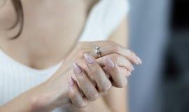 Las manos de la mujer con el anillo de la petici?n del matrimonio Mujer joven con la manicura imagen de archivo