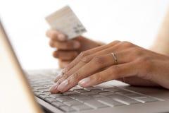 Las manos de la mujer con el teclado y la tarjeta de crédito fotos de archivo