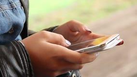 Las manos de la mujer con el teléfono del tacto enrollan los mensajes que mecanografían los fingeres del SMS metrajes