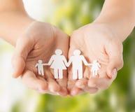 Las manos de la mujer con la familia de papel del hombre Fotografía de archivo libre de regalías