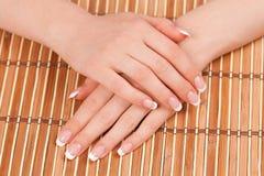 Las manos de la mujer con la manicura francesa perfecta Imagen de archivo libre de regalías