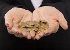 Las manos de la mujer con las monedas de un oro Imágenes de archivo libres de regalías