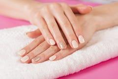 Las manos de la mujer con los clavos manicure en la toalla blanca Fotos de archivo libres de regalías