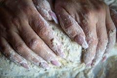 Las manos de la mujer con los clavos manicured funcionan con pasta en la cocina fotos de archivo