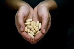 Las manos de la mujer con las píldoras encendido imagen de archivo libre de regalías