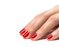 Las manos de la mujer con rojo manicured clavan el primer. Imagen de archivo libre de regalías