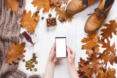 Las manos de la mujer con smartphone pagan hacer compras en línea con ropa y accesorios del otoño del inconformista en un fondo d Fotografía de archivo libre de regalías