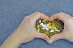 Las manos de la mujer crearon una forma del coraz?n P?ldoras blancas y amarillas Imite para arriba para las ofertas especiales co foto de archivo libre de regalías