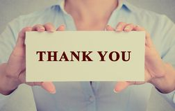 Las manos de la mujer de negocios que sostienen la muestra o la tarjeta con el mensaje le agradecen Imagen de archivo libre de regalías