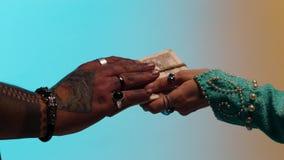 Las manos de la mujer del este con muchos anillos que daban el dinero implicaron con guita al hombre del vendedor, aislado en ama almacen de video