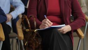 Las manos de la mujer del primer que hacen notas durante seminario almacen de metraje de vídeo