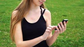 Las manos de la mujer del primer usando pantalla táctil llaman por teléfono al aire libre en parque de la ciudad Imagenes de archivo