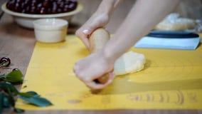 Las manos de la mujer desarrollan la pasta en la tabla de cocina para hacer una empanada con las bayas almacen de video